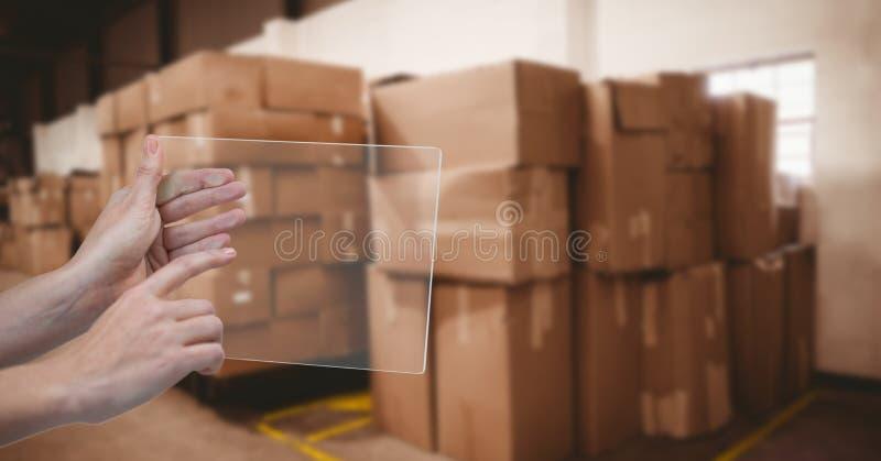 Χέρι που χρησιμοποιεί τη διαφανή συσκευή στην αποθήκη εμπορευμάτων στοκ εικόνες