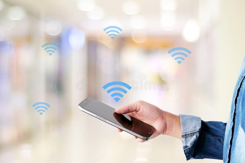 Χέρι που χρησιμοποιεί το έξυπνο εικονίδιο τηλεφώνων και wifi πέρα από το υπόβαθρο θαμπάδων, ψηφίο στοκ εικόνες