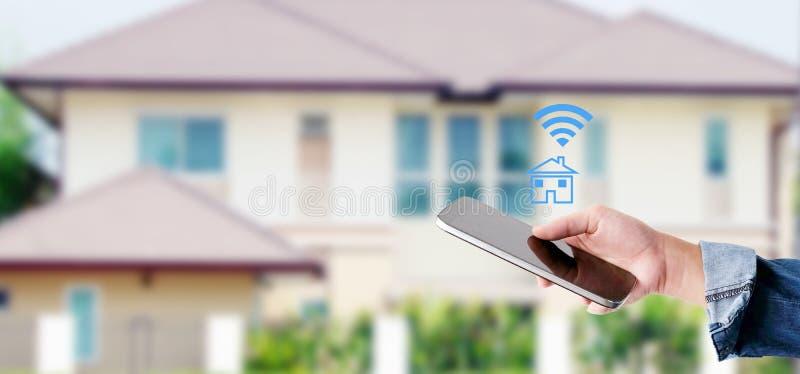Χέρι που χρησιμοποιεί το έξυπνο τηλέφωνο με το έξυπνο εικονίδιο εγχώριου ελέγχου πέρα από το υπόβαθρο σπιτιών θαμπάδων, έξυπνη έν στοκ φωτογραφία με δικαίωμα ελεύθερης χρήσης