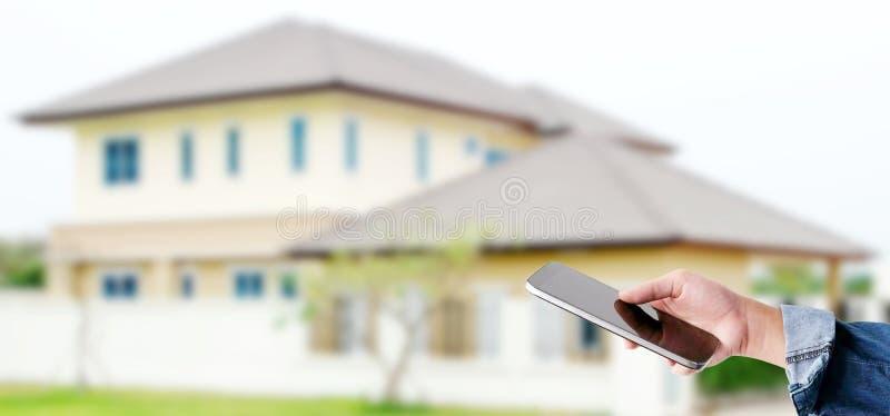 Χέρι που χρησιμοποιεί το έξυπνο τηλέφωνο πέρα από το υπόβαθρο σπιτιών θαμπάδων, έμβλημα, έξυπνη έννοια εγχώριου ελέγχου στοκ εικόνες με δικαίωμα ελεύθερης χρήσης