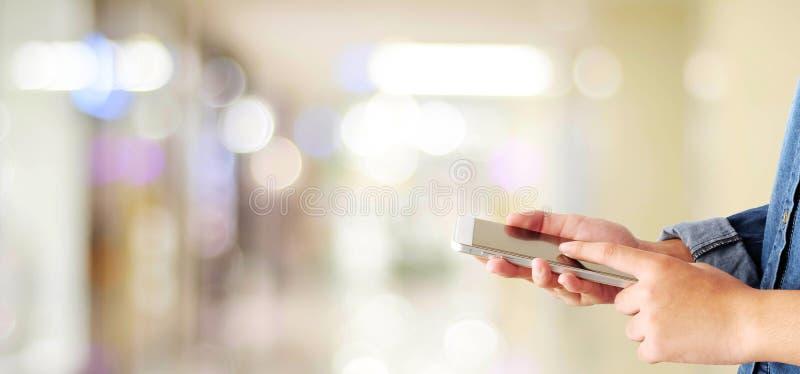 Χέρι που χρησιμοποιεί το έξυπνο τηλέφωνο πέρα από το κατάστημα θαμπάδων με το ελαφρύ backgrou bokeh στοκ εικόνες