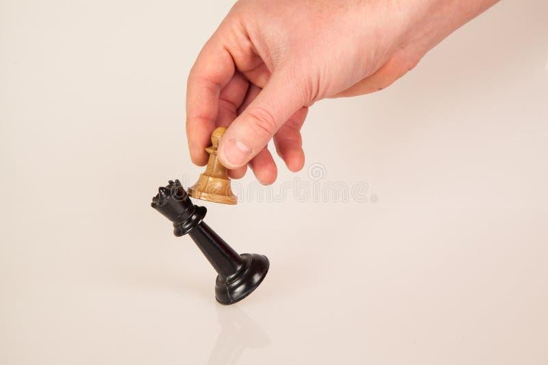 Χέρι που χτυπά πάνω από έναν αριθμό βασιλιάδων σκακιού με το άσπρο ενέχυρο Παιχνίδι επιτυχίας ανταγωνισμού έννοια στρατηγικής, δι στοκ εικόνα