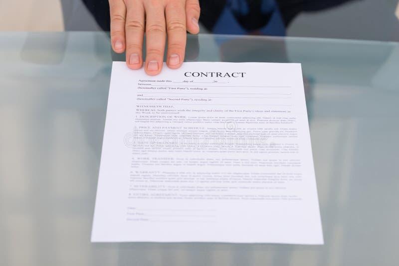Χέρι προσώπου με το έγγραφο συμβάσεων στοκ φωτογραφία