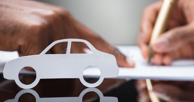 Χέρι προσώπων ` s που υπογράφει τη σύμβαση συμφωνίας δανείου αυτοκινήτων στοκ εικόνα