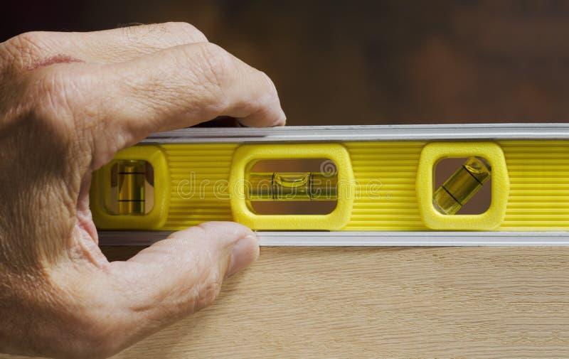 Χέρι στο επίπεδο ξυλουργών στοκ φωτογραφία με δικαίωμα ελεύθερης χρήσης