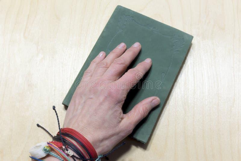 Χέρι στο πράσινο περιοδικό πέρα από τον πίνακα στοκ φωτογραφία με δικαίωμα ελεύθερης χρήσης