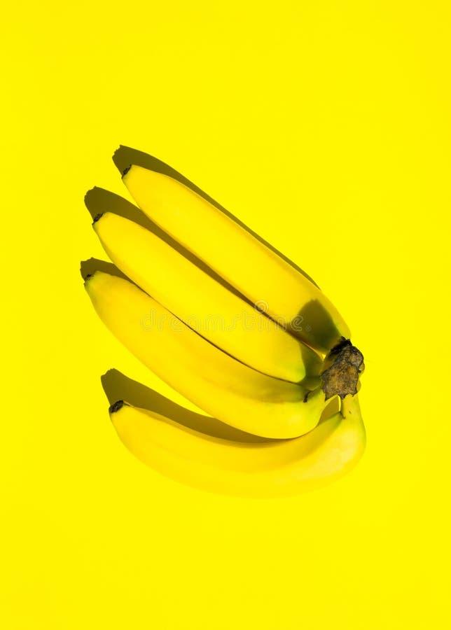 Χέρι συστάδων των μπανανών στις σταθερές κίτρινες βάσεις μονοχρωματικός Φωτεινή ισχυρή σκιά φωτός του ήλιου Καθιερώνον τη μόδα φο στοκ εικόνες με δικαίωμα ελεύθερης χρήσης