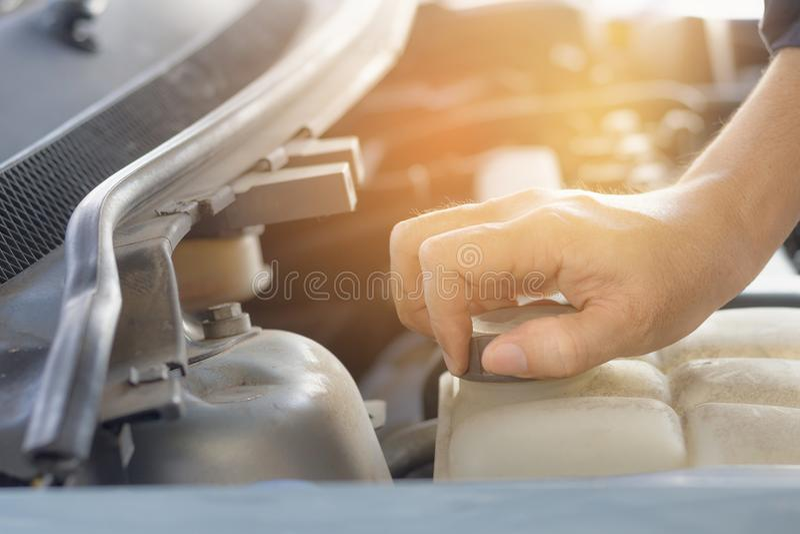 Χέρι της ανοικτής ΚΑΠ δεξαμενής νερού ατόμων του αυτοκινήτου για τη συντήρηση στοκ φωτογραφίες