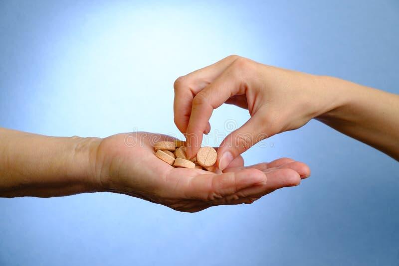 Χέρι της νέας γυναίκας και της ηλικιωμένης γυναίκας που κρατούν τα χάπια στοκ φωτογραφίες