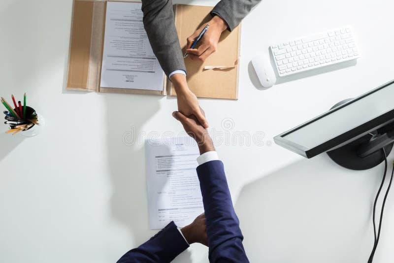 Χέρι τινάγματος Businessperson με τον υποψήφιο πέρα από το άσπρο γραφείο στοκ φωτογραφία με δικαίωμα ελεύθερης χρήσης