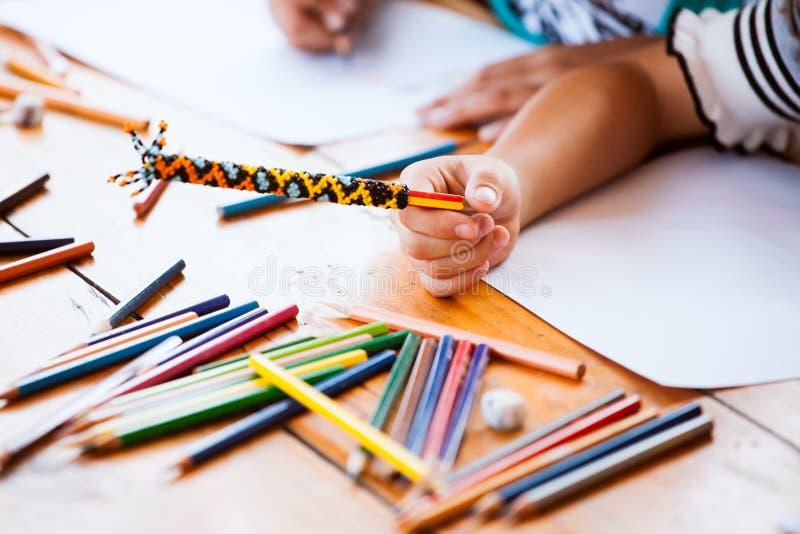 Χέρι του ασιατικού κραγιονιού εκμετάλλευσης κοριτσιών παιδιών για το σχεδιασμό και τη ζωγραφική στοκ φωτογραφία