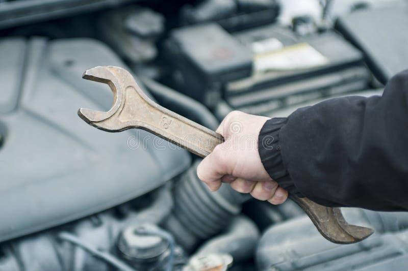 Χέρι του αυτόματου μηχανικού με ένα γαλλικό κλειδί Επισκευή αυτοκινήτων Χέρι με το γαλλικό κλειδί Αυτόματος μηχανικός στην επισκε στοκ φωτογραφία