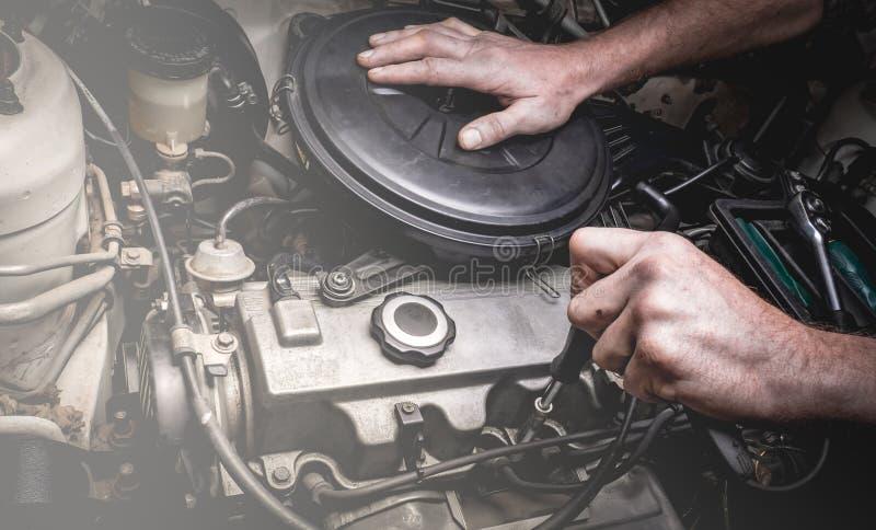 Χέρι του αυτόματου μηχανικού με ένα γαλλικό κλειδί στοκ εικόνα