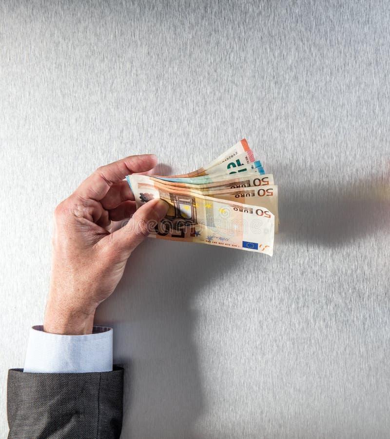 Χέρι του επιχειρηματία που κρατά τα ευρο- τραπεζογραμμάτια για τα εταιρικά χρήματα στοκ εικόνες με δικαίωμα ελεύθερης χρήσης