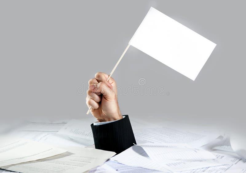 Χέρι του επιχειρηματία που προκύπτει από το φορτωμένο γραφείο γραφικής εργασίας που κρατά την άσπρη σημαία στοκ εικόνες