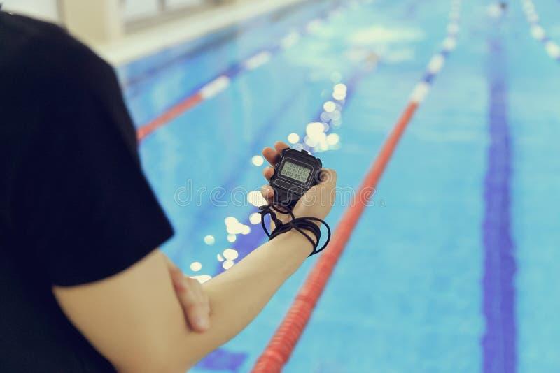 Χέρι του λεωφορείου με ένα χρονόμετρο με διακόπτη κατά τη διάρκεια των ανταγωνισμών στην πισίνα στοκ φωτογραφία