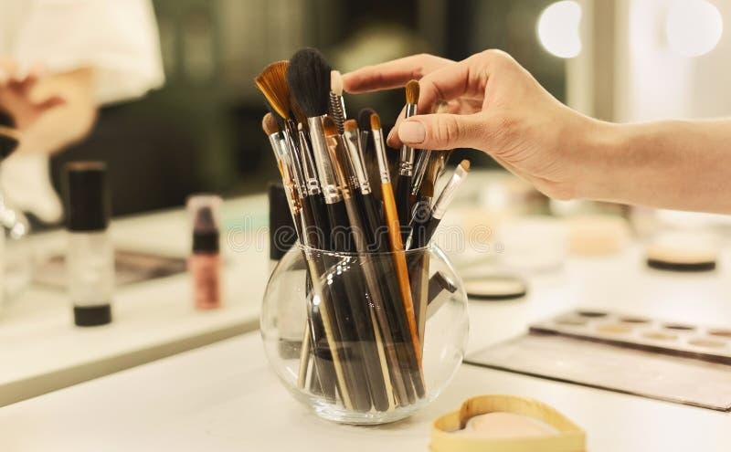 Χέρι του καλλιτέχνη Makeup που παίρνει τη βούρτσα από το βάζο με τα επαγγελματικά εργαλεία στοκ φωτογραφία με δικαίωμα ελεύθερης χρήσης