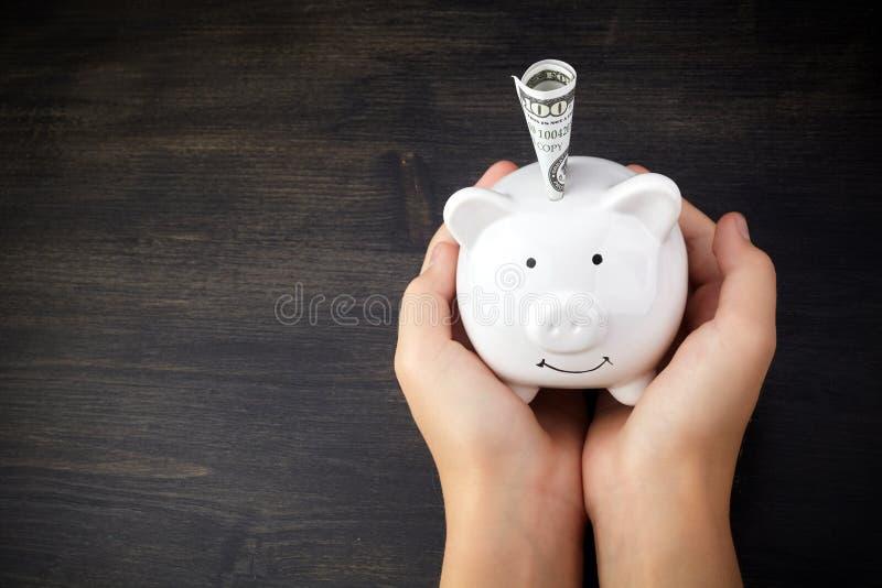 Χέρι του κοριτσιού που κρατά την άσπρη piggy τράπεζα στο ξύλινο υπόβαθρο με το διάστημα αντιγράφων στοκ εικόνα