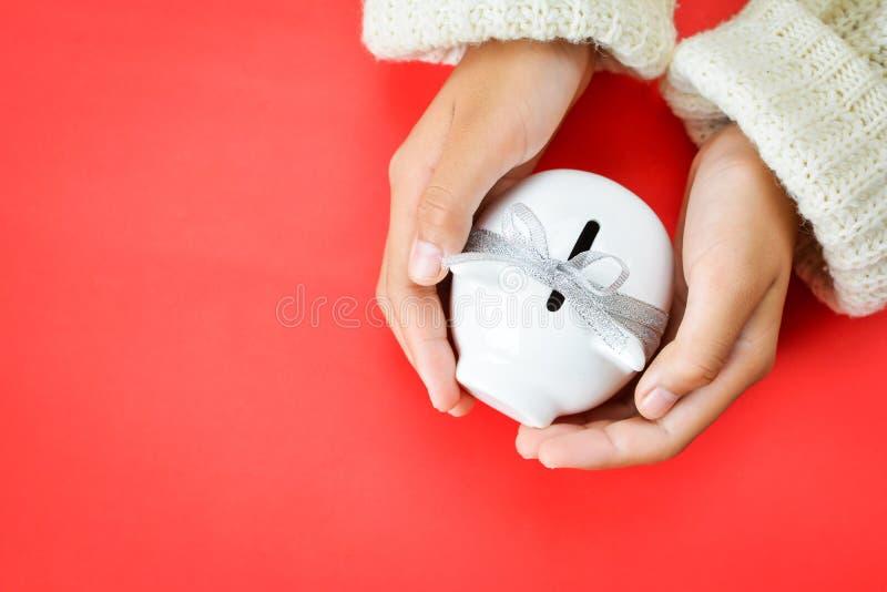 Χέρι του κοριτσιού που κρατά τον άσπρο piggy τύπο τραπεζών και κορδελλών στο κόκκινο υπόβαθρο στοκ φωτογραφίες