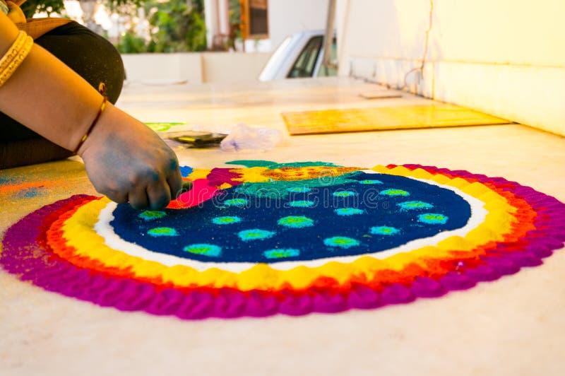 Χέρι του νέου ινδικού κοριτσιού που κάνει το rangoli από τη χρωματισμένη σκόνη στην παραμονή diwali στοκ εικόνα