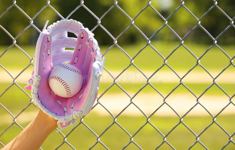 Χέρι του παίχτη του μπέιζμπολ με το ρόδινες γάντι και τη σφαίρα στοκ εικόνα με δικαίωμα ελεύθερης χρήσης