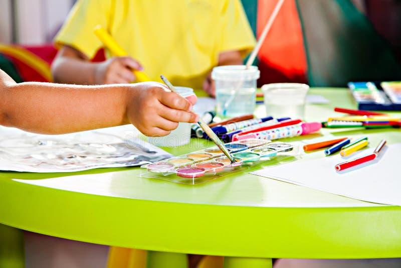 Χέρι του παιδιού με το πινέλο στο σύνολο watercolor στοκ εικόνα