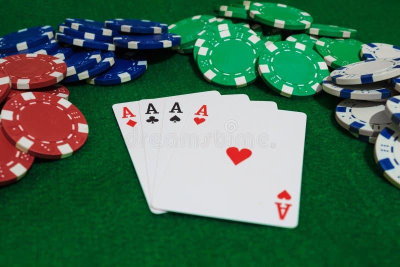 Χέρι του πόκερ, τεσσάρων άσσων και τσιπ σε ένα αισθητό πράσινο υπόβαθρο Όψη προοπτικής στοκ φωτογραφίες με δικαίωμα ελεύθερης χρήσης
