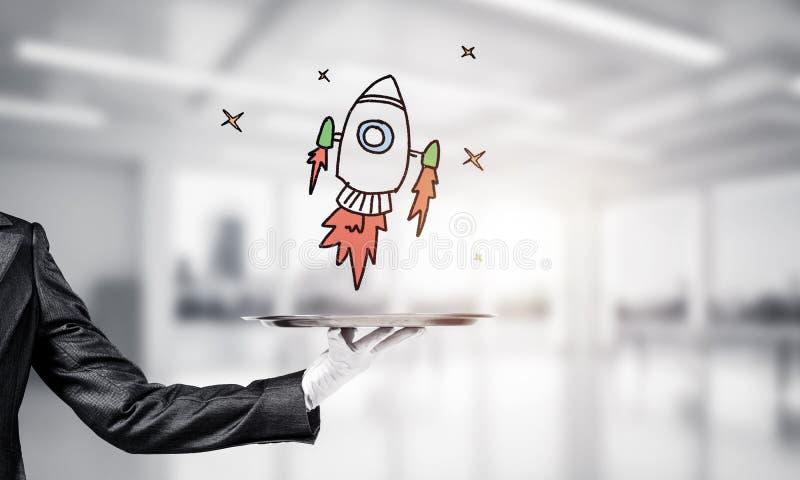 Χέρι του σερβιτόρου που παρουσιάζει το σκιαγραφημένο πύραυλο στο δίσκο στοκ φωτογραφίες