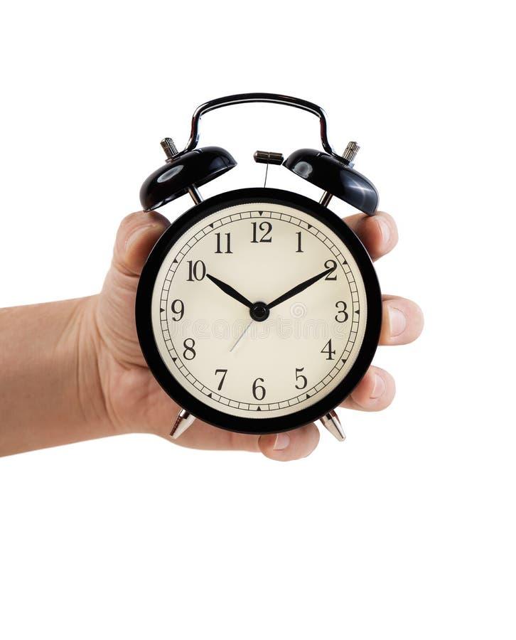 Χέρι το αναδρομικό ξυπνητήρι ύφους, που απομονώνεται που κρατά στο λευκό στοκ φωτογραφίες