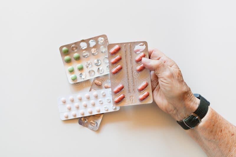Χέρι των ηλικιωμένων χαπιών εκμετάλλευσης γυναικών και της ιατρικής, άσπρο υπόβαθρο στοκ φωτογραφία με δικαίωμα ελεύθερης χρήσης