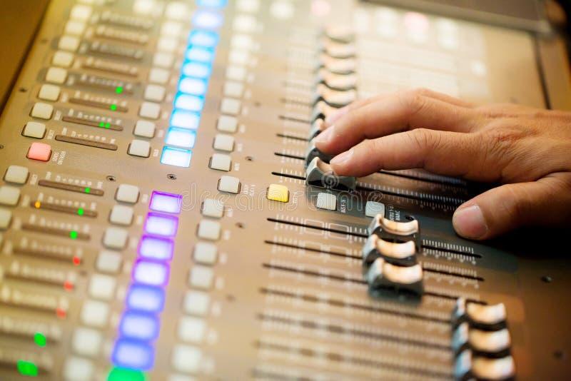 Χέρι φωτογραφιών θαμπάδων που ρυθμίζει τον ακουστικό αναμίκτη Υγιή χέρια μηχανικών που λειτουργούν στον υγιή αναμίκτη στη ζωντανή στοκ εικόνες