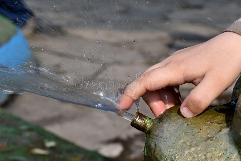Χέρι χρονών του αγοριού 5 σχετικά με το ρεύμα νερού από την πηγή στοκ εικόνες
