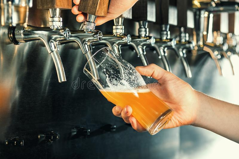 Χέρι bartender που χύνει μια μεγάλη μπύρα ξανθού γερμανικού ζύού στη βρύση στοκ εικόνες με δικαίωμα ελεύθερης χρήσης