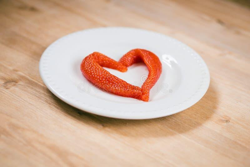 Χαβιάρι σολομών με μορφή της καρδιάς στο πιάτο α στον ξύλινο πίνακα στοκ εικόνες με δικαίωμα ελεύθερης χρήσης