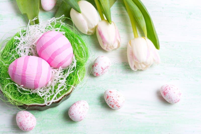 Χαιρετισμός Πάσχας με τις άσπρες τουλίπες και τα ρόδινα αυγά στη φωλιά στοκ εικόνα με δικαίωμα ελεύθερης χρήσης