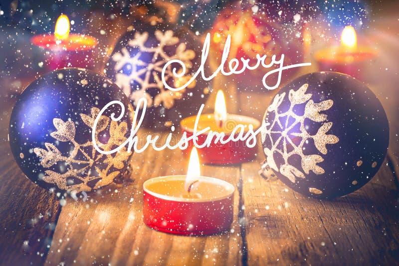 χαιρετισμός Χριστουγέννων καρτών Οι φωτεινές κόκκινες μπλε σφαίρες με snowflake τη διακόσμηση άναψαν τα κεριά στο παλαιό ξύλινο υ απεικόνιση αποθεμάτων