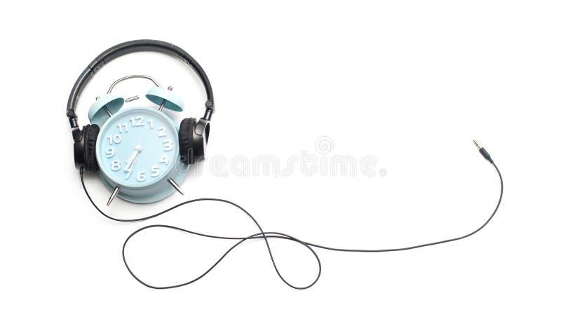 χαλάρωση έννοιας Ξυπνητήρι και ακουστικό που απομονώνονται στοκ φωτογραφία