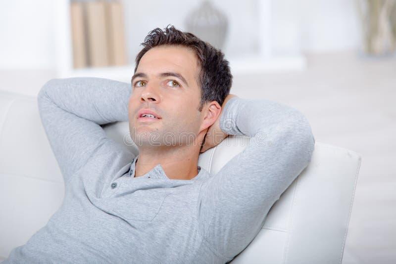 Χαλάρωση ατόμων στον καναπέ στο σπίτι στοκ φωτογραφίες με δικαίωμα ελεύθερης χρήσης