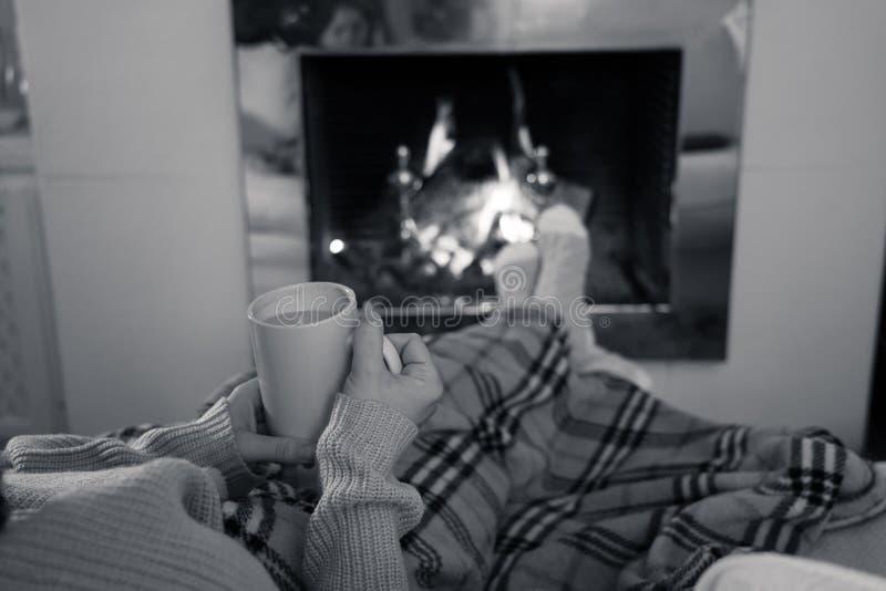 Χαλάρωση γυναικών από την εστία που θερμαίνει τα πόδια σε μάλλινο με ένα φλυτζάνι των καυτών καλτσών και του καλύμματος ποτών στοκ φωτογραφίες