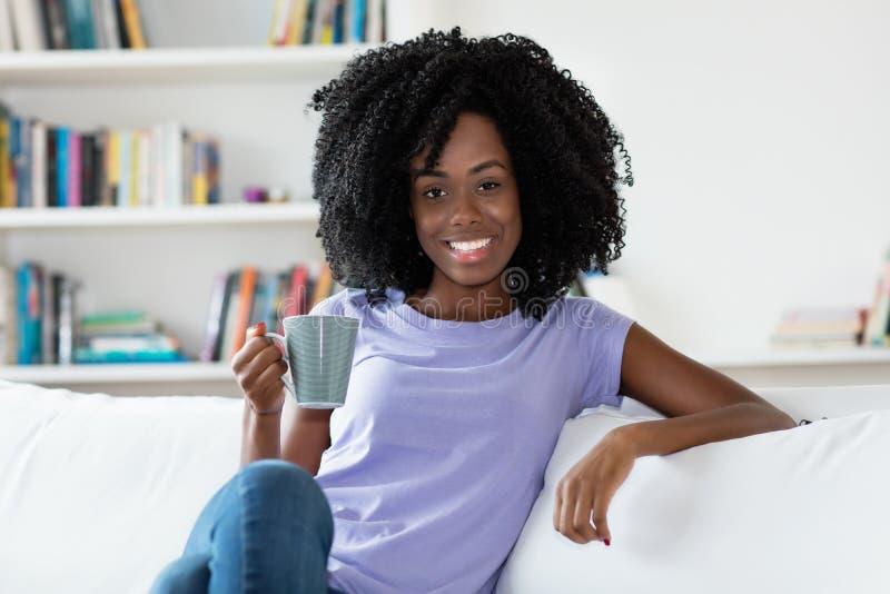Χαλάρωση γυναικών αφροαμερικάνων με το φλιτζάνι του καφέ στοκ εικόνα με δικαίωμα ελεύθερης χρήσης