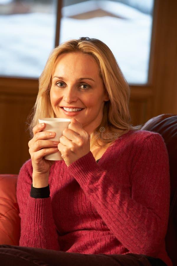 Χαλάρωση γυναικών με το ζεστό ποτό στον καναπέ που προσέχει τη TV στοκ φωτογραφίες με δικαίωμα ελεύθερης χρήσης