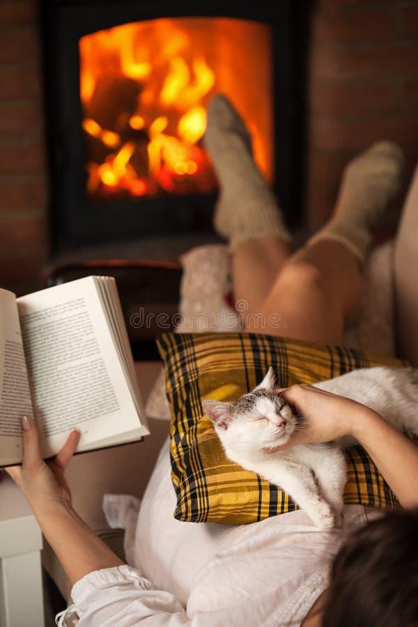 Χαλάρωση γυναικών στην εστία με ένα βιβλίο και το γατάκι της στοκ εικόνες
