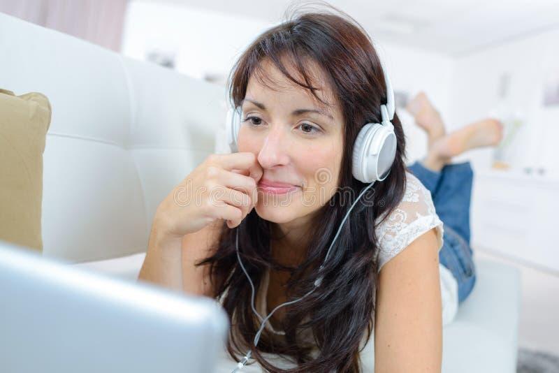 Χαλάρωση γυναικών στον καναπέ που χαμογελά και που προσέχει κάτι στο lap-top στοκ εικόνες με δικαίωμα ελεύθερης χρήσης