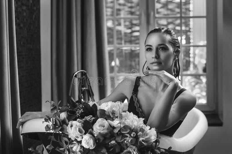Χαλάρωση γυναικών στο λουτρό με τα λουλούδια, οργανική φροντίδα δέρματος, luxury spa ξενοδοχείο, φωτογραφία τρόπου ζωής στοκ εικόνα με δικαίωμα ελεύθερης χρήσης