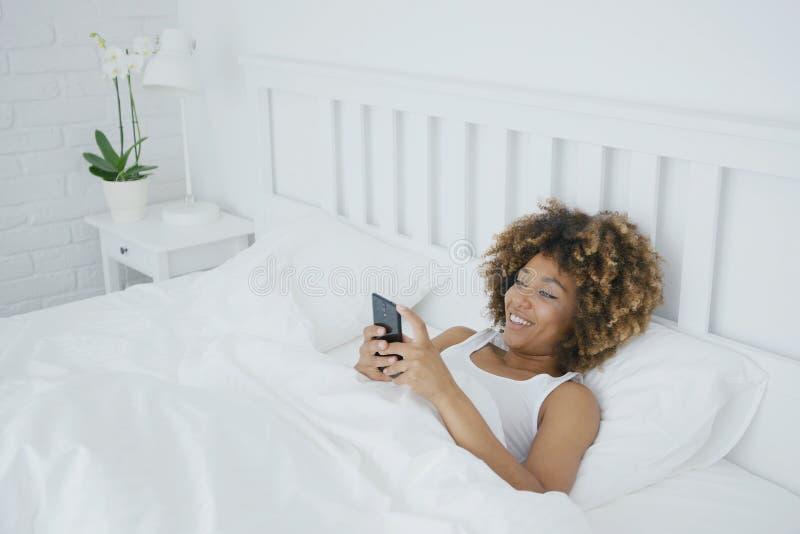 Χαλάρωση γυναικών χαμόγελου με το τηλέφωνο στο κρεβάτι στοκ εικόνες