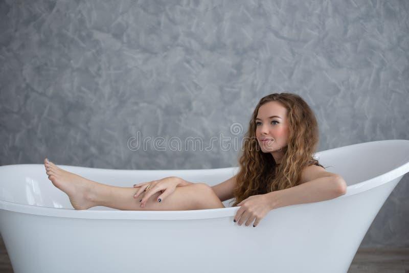 Χαλάρωση γυναικών χαμόγελου στην μπανιέρα στοκ εικόνα