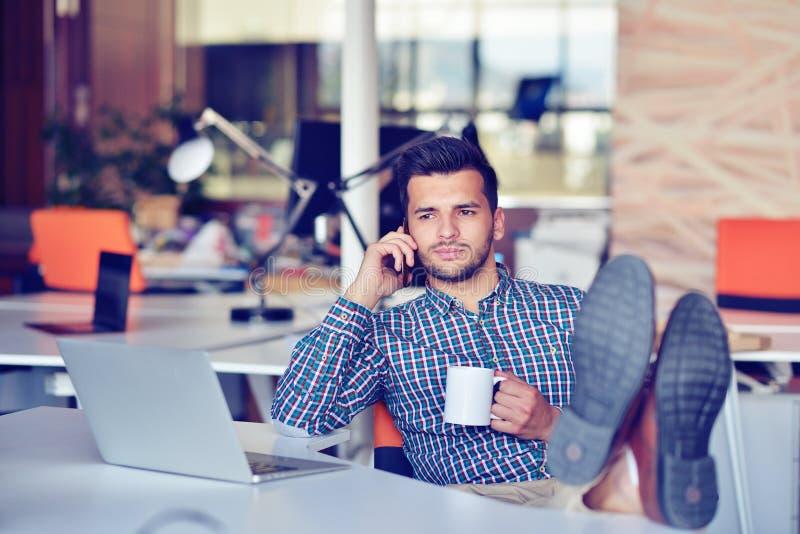 Χαλάρωση επιχειρηματιών με τα πόδια επάνω στο γραφείο, καφές κατανάλωσης ονειρεμένος για το μέλλον στον εργασιακό χώρο στο σύγχρο στοκ εικόνες με δικαίωμα ελεύθερης χρήσης