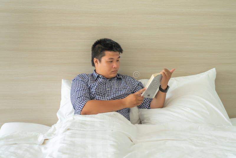 Χαλάρωση επιχειρηματιών με την ανάγνωση του βιβλίου πριν από το χρόνο κρεβατιών στοκ εικόνες