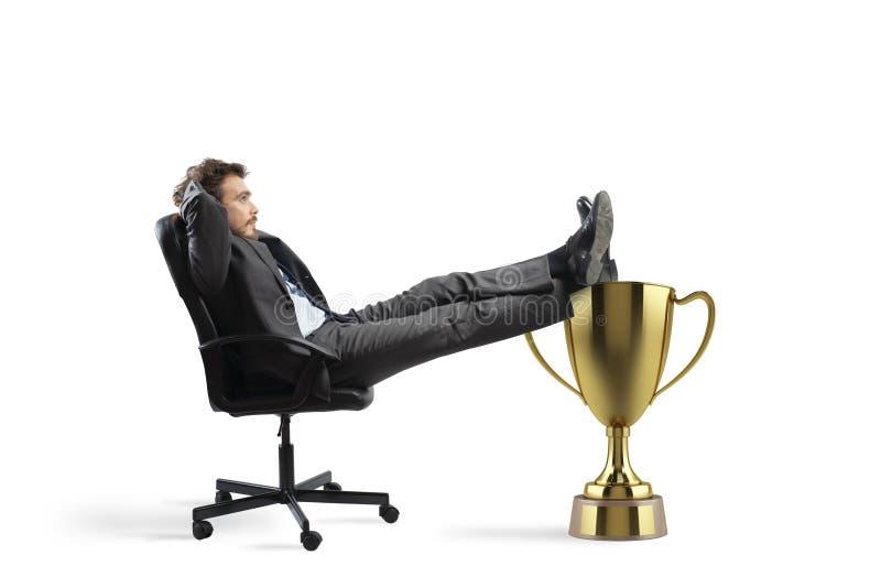 Χαλάρωση επιχειρηματιών νικητών πέρα από ένα χρυσό φλυτζάνι στοκ φωτογραφία
