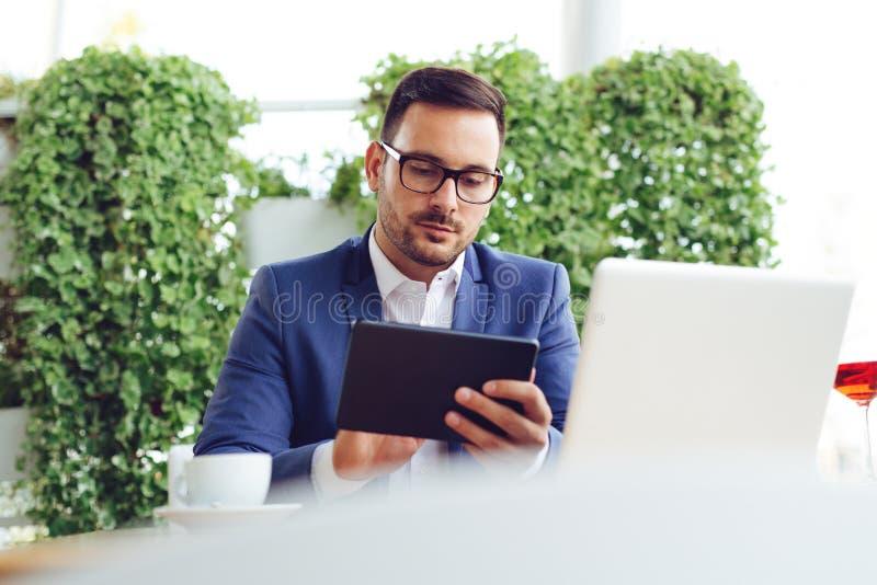 Χαλάρωση επιχειρηματιών στο φραγμό και κατοχή ενός διαλείμματος, χρησιμοποιεί μια ψηφιακή ταμπλέτα και πίνει ένα espresso στοκ φωτογραφία